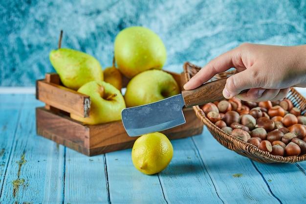 Schneiden zitrone auf blauem tisch mit holzkorb von äpfeln und nüssen.