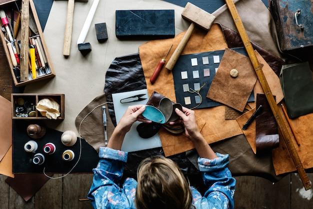Schneider, der leathercraft-ausrüstung auf dem tisch macht
