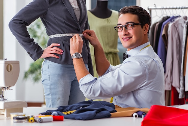 Schneider des jungen mannes, der mit weiblichem kunden arbeitet