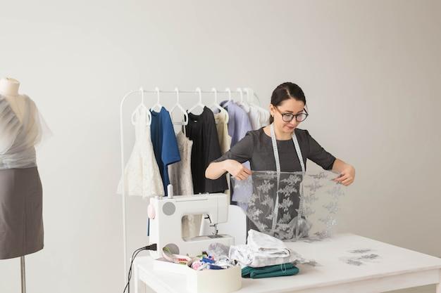 Schneider-, schneider-, mode- und ausstellungsraumkonzept - porträt einer talentierten schneiderin, die mit textilien zum nähen von kleidung arbeitet.