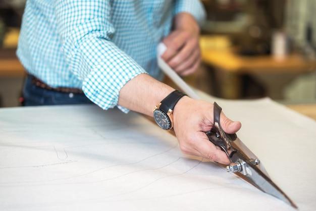 Schneider schneidet das markierte muster auf stoff mit einer großen schere auf der werkbank in seinem laden aus