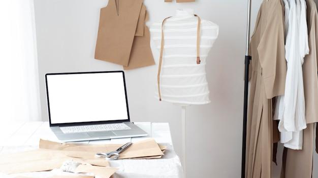Schneiderei mit kleiderform und laptop