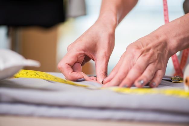 Schneiderhände, die an neuer kleidung arbeiten