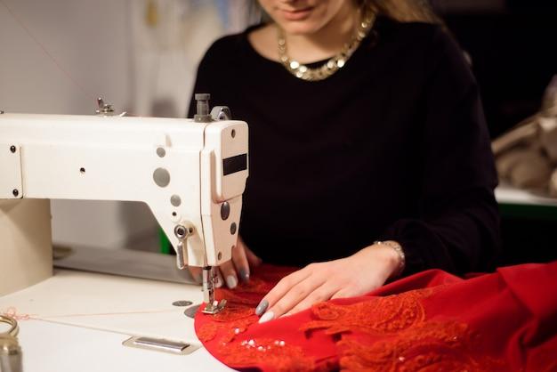 Schneiderin, die an der nähmaschine arbeitet. schneider, der ein kleidungsstück herstellt. hobbynähen als kleinunternehmerkonzept.