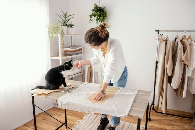 Schneiderin, die im studio mit katze arbeitet