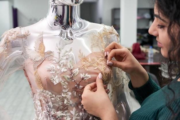 Schneiderin, die weißes spitzenhochzeitskleid auf einem mannequin im schneiderstudio fixiert