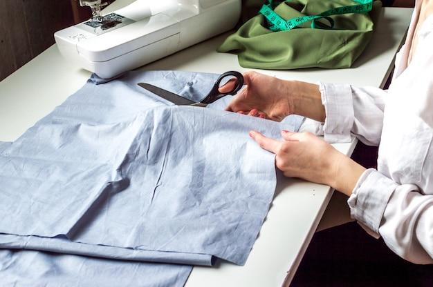 Schneiderin macht das schneiden von stoffen auf dem desktop. schneiderei im atelier. bekleidungsherstellung, nähprozess