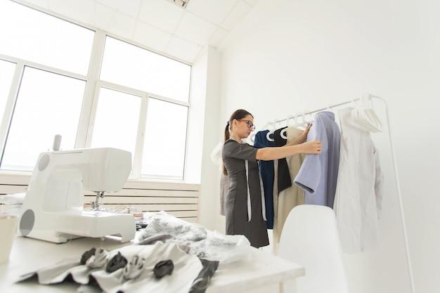 Schneiderin, modedesignerin, schneiderin und menschenkonzept - modedesignerin der jungen frau in ihrem ausstellungsraum.