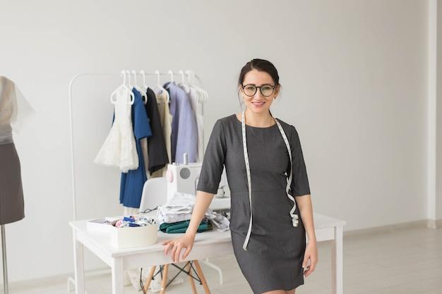 Schneiderin, modedesignerin, schneiderin und menschenkonzept - schöne modedesignerin stehend