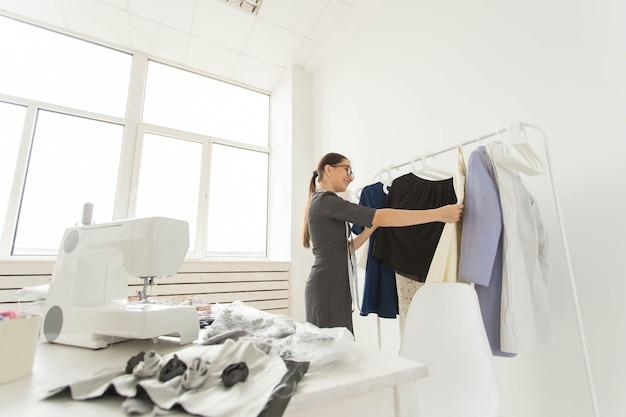 Schneiderin, modedesignerin, schneiderin und people-konzept - junge modedesignerin in ihrem showroom