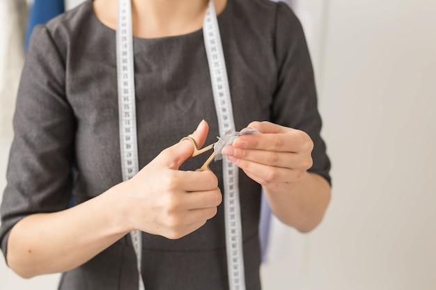 Schneiderin, modedesignerin und schneiderin - seamstress und ihre hände schließen sich in der werkstatt
