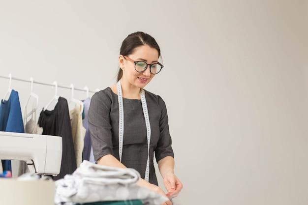 Schneiderin, modedesignerin und schneiderkonzept - junge modedesignerin arbeitet in ihrem showroom.