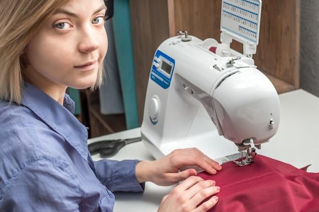 Schneiderin näht kleidung auf einer nähmaschine. konzept-nähwerkstatt. schneiderei-prozess. designer, modedesigner