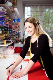 Schneiderin schneidet kleiderstoff auf skizzenlinie mit nähmaschine. geschäftsinhaber shop und unternehmerkonzept.