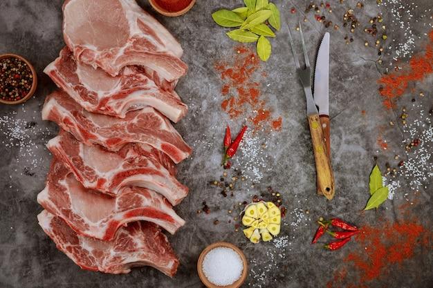 Schneidet rohe schweinekoteletts rippe mit gewürzen und messer auf grauer oberfläche