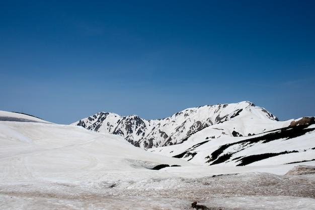 Schneien sie auf bergen und ansicht des blauen himmels an murodo-station alpinen weges tateyama kurobe, japan-alpen