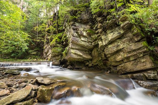 Schnell fließender flussstrom mit glattem seidigem wasser, das von großen steinen in schönen wasserfällen an hellem sonnigem sommertag fällt.