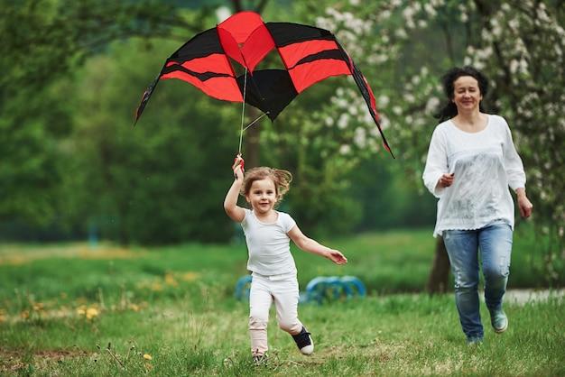 Schnell und aktiv. positives weibliches kind und großmutter, die mit rotem und schwarzem drachen in den händen draußen laufen