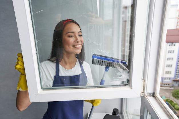 Schnell und effizient. attraktive junge frau, die beim reinigen des fensters mit rakel lächelt. hausarbeit und housekeeping, reinigungsservicekonzept
