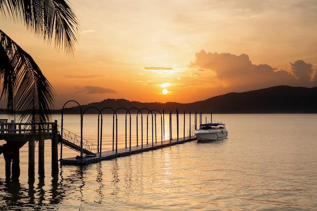 Schnellboot auf dem sich hin- und herbewegenden pier mit schönem sonnenuntergang