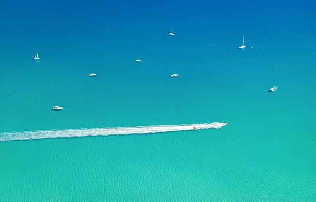 Schnellboot und wellenschieber hinterlassen spuren auf dem wasser mit anderen booten und dem meer als hintergrund