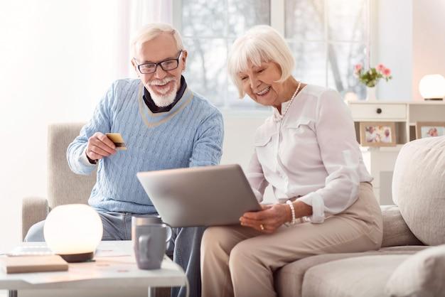 Schnelle bezahlung. fröhlicher älterer mann, der seiner frau seine kreditkarte gibt, während sie durch einen online-shop schauen und etwas kaufen