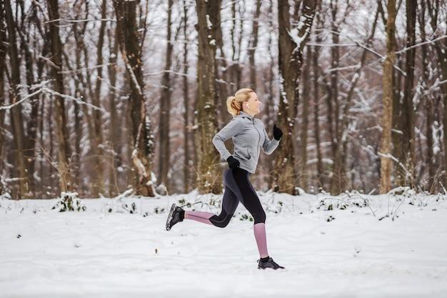 Schnelle schlanke sportlerin, die im wald am verschneiten wintertag läuft. rennen, joggen in der natur, winterfitness