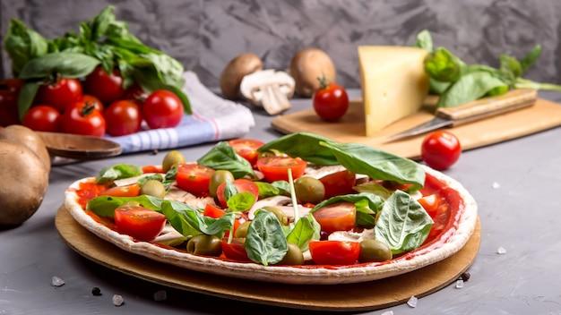 Schnelle selbst gemachte vegetarische pizza mit pilzen auf einer grauen tabelle