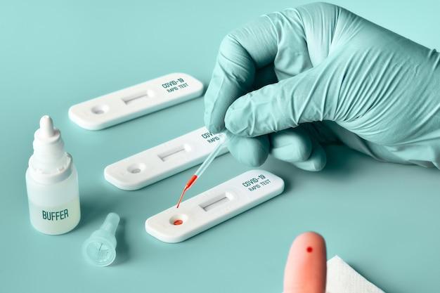 Schneller express-covid19-test. der arzt oder die ärztin trägt beim test blut vom finger des patienten auf.