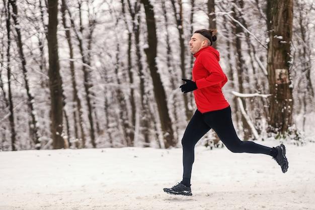 Schneller läufer, der am verschneiten wintertag im wald läuft. marathon, winterfitness, gesunde gewohnheiten