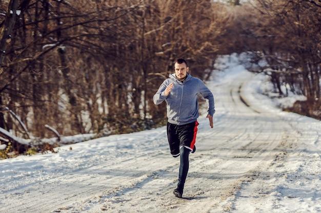 Schneller läufer, der auf schneebedecktem weg in der natur am sonnigen wintertag läuft