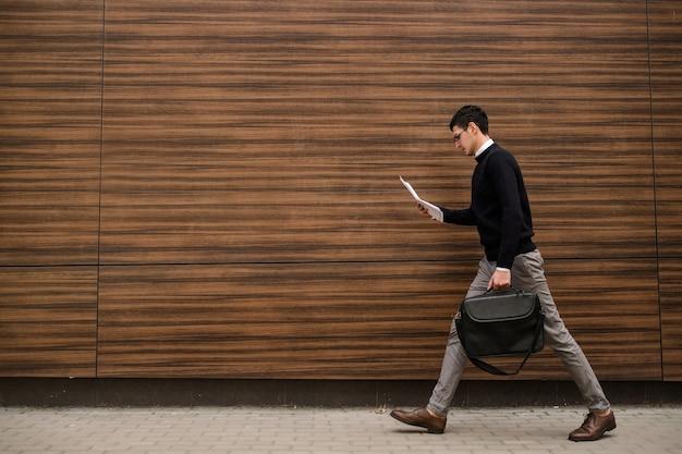Schneller, moderner geschäftslebensstil. schneller arbeitsmodus. lässiger büromann, der unterwegs dokumente liest. holz textur hintergrund. freiraumkonzept