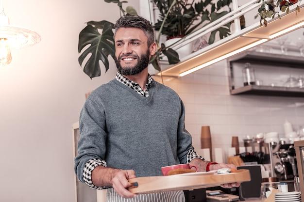 Schneller service. freudiger angenehmer mann, der lächelt, während er ordnung zum tisch bringt