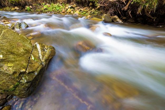 Schnelles fließen durch wilden grünen waldfluss mit kristallklarem glattem seidigem wasser, das von großen nassen steinen in schönen wasserfällen an hellem sonnigem sommertag fällt. langzeitbelichtung.