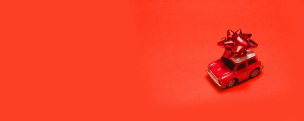 Schnelles lieferkonzept. rotes automodellspielzeug mit bogen auf rotem hintergrund