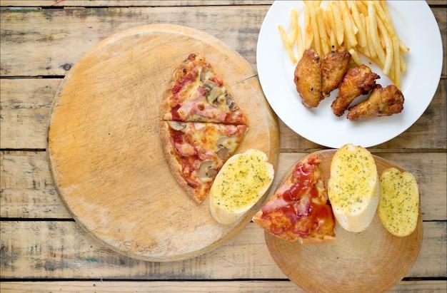 Schnellimbiß, knusperige hühnerflügel, brot, pommes-frites und pizza auf hölzernem hintergrund