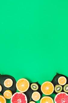 Schnitt von bunten frischen tropischen früchten auf grünem hintergrund