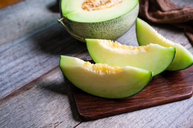 Schnitt von frischer süßer grüner melone auf holz