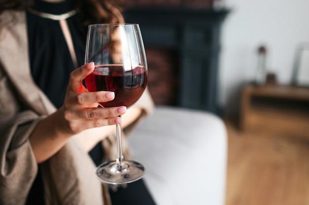 Schnittansicht der hand der frau, die glas rotwein hält. model tragen schwarzes kleid und braunen schal. frau allein im wohnzimmer.