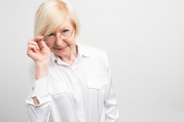 Schnittansicht der reifen frau, die einen teil ihrer brille hält und geradeaus schaut. manchmal können alte menschen zu pünktlich und zu nervig mit verachtung sein.