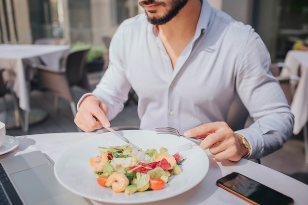 Schnittansicht des bärtigen jungen mannes, der am tisch sitzt und salat isst. es sind laptop und telefon auf dem bild.