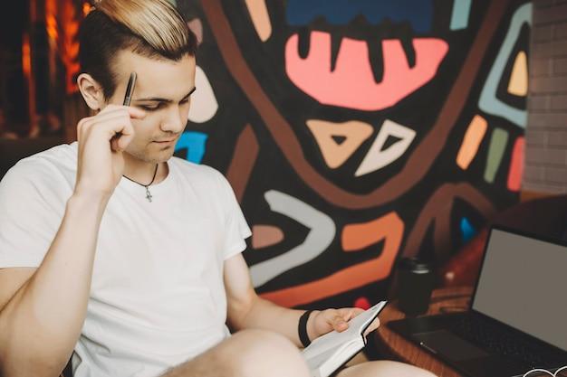 Schnittansicht des gutaussehenden mannes im weißen hemd, das bequem am runden tisch mit laptop sitzt und aufmerksam auf notizblock schaut