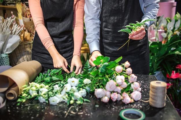 Schnittansicht des jungen mannes und der jungen frau in der schwarzen schürze stehen am tisch. sie machen blumensträuße aus weißen und hellrosa rosen. er fügte einige blattfarne hinzu.
