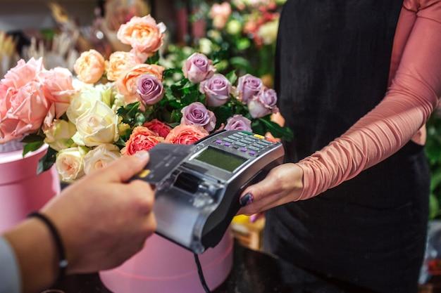 Schnittansicht des mannes, der kreditkarte über geldtherminal hält. er bezahlt für blumen. junge floristin halten geld therminal. viele blumen sind hinter ihr.