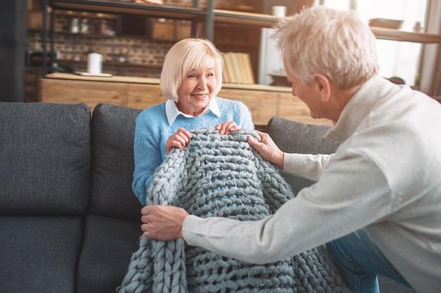 Schnittansicht eines alten mannes, der seiner frau eine graue decke gibt. er kümmert sich