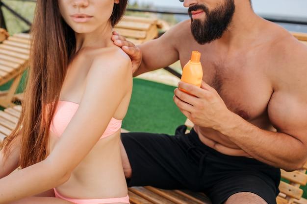 Schnittansicht von mann und frau sitzend. sie schaut geradeaus. guy trägt eine sonnenfeste lotion auf schultern und rücken auf. er ist vorsichtig.