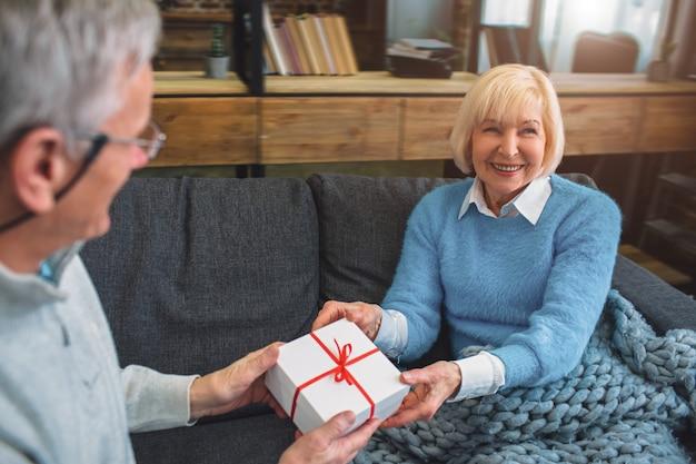 Schnittansicht von netten und niedlichen großeltern. er gibt seiner frau ein geschenk