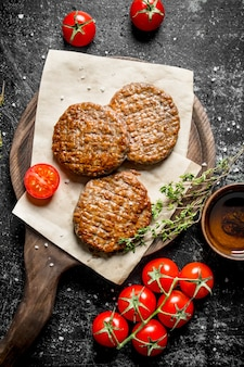 Schnitzel auf papier mit thymian und tomaten auf einem ast. auf schwarzem rustikalem hintergrund