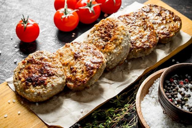 Schnitzel auf papier mit tomaten. auf dunklem rustikalem hintergrund