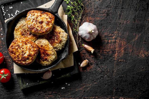 Schnitzel in einer pfanne auf papier mit thymian, knoblauch und tomaten auf dunklem holztisch